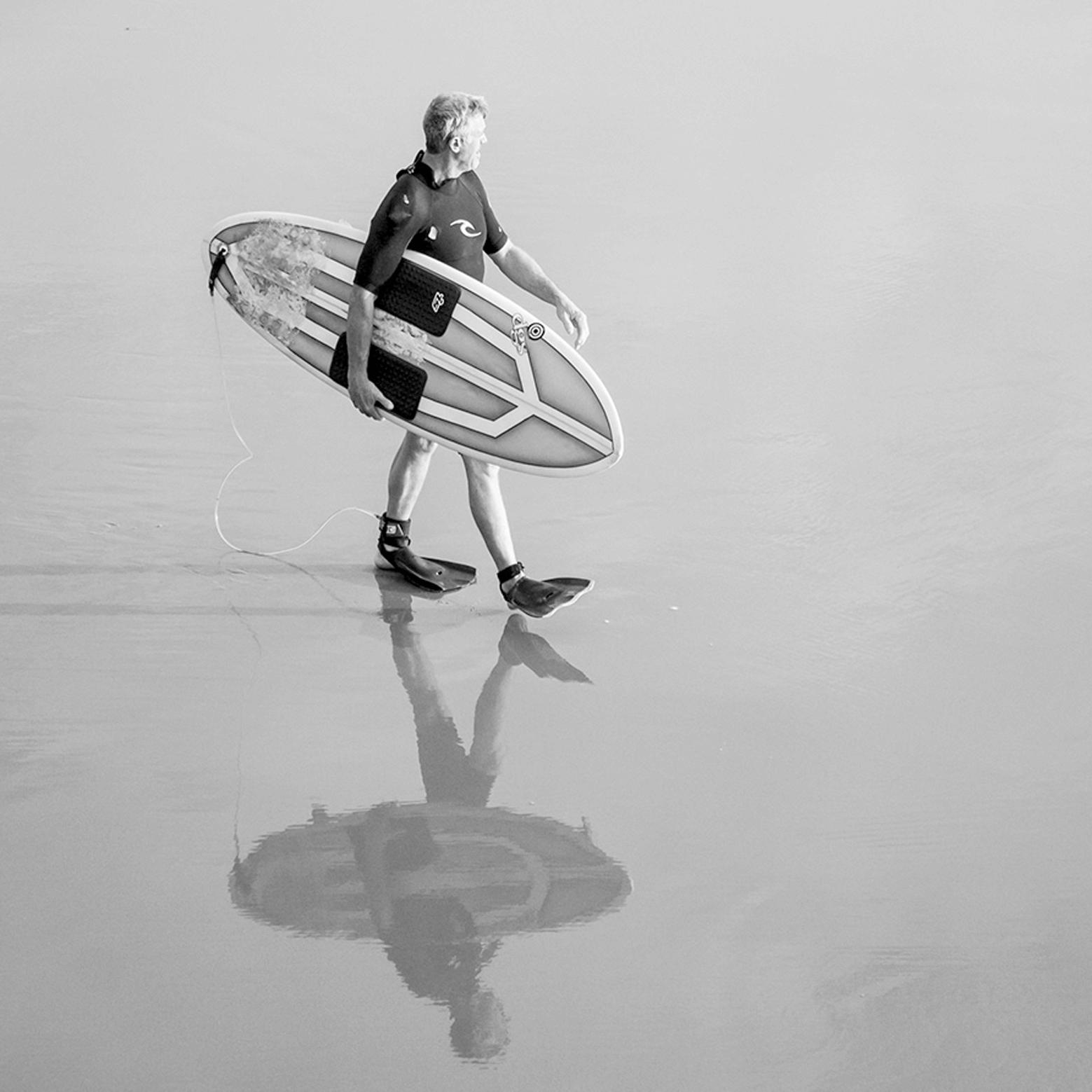 man walking on the beach, reflection on water, surfer, beach, walking, surfing, durban, sport photography.